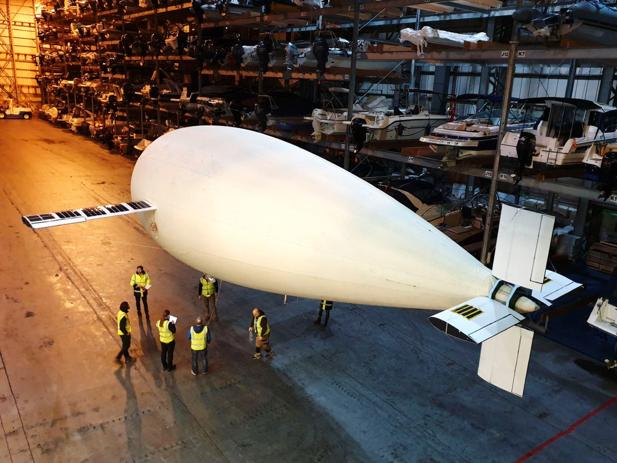 A blimp in a hanger above people.