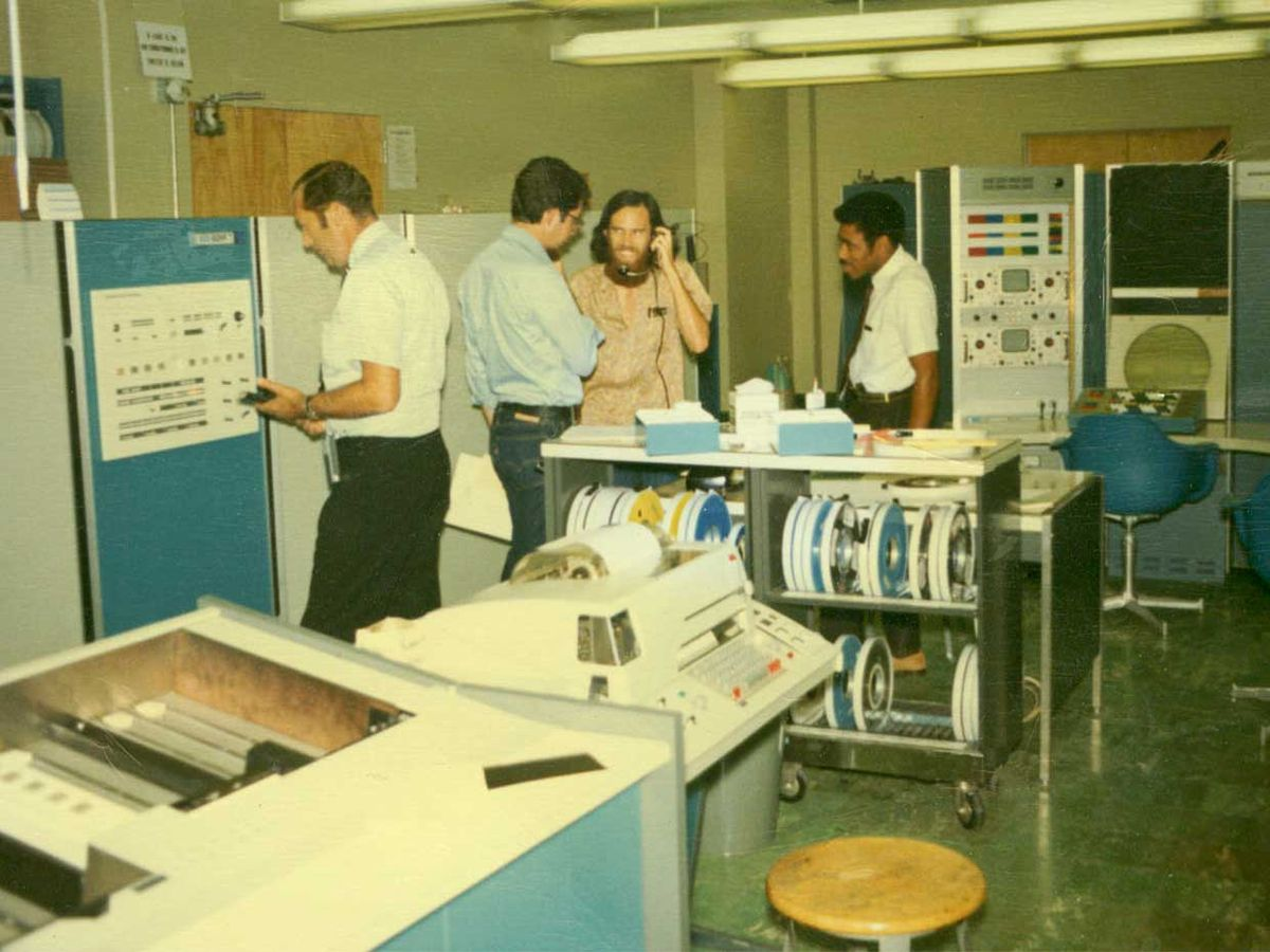 Four men stand in UCLA's 3420 Boelter Hall in the 1960s