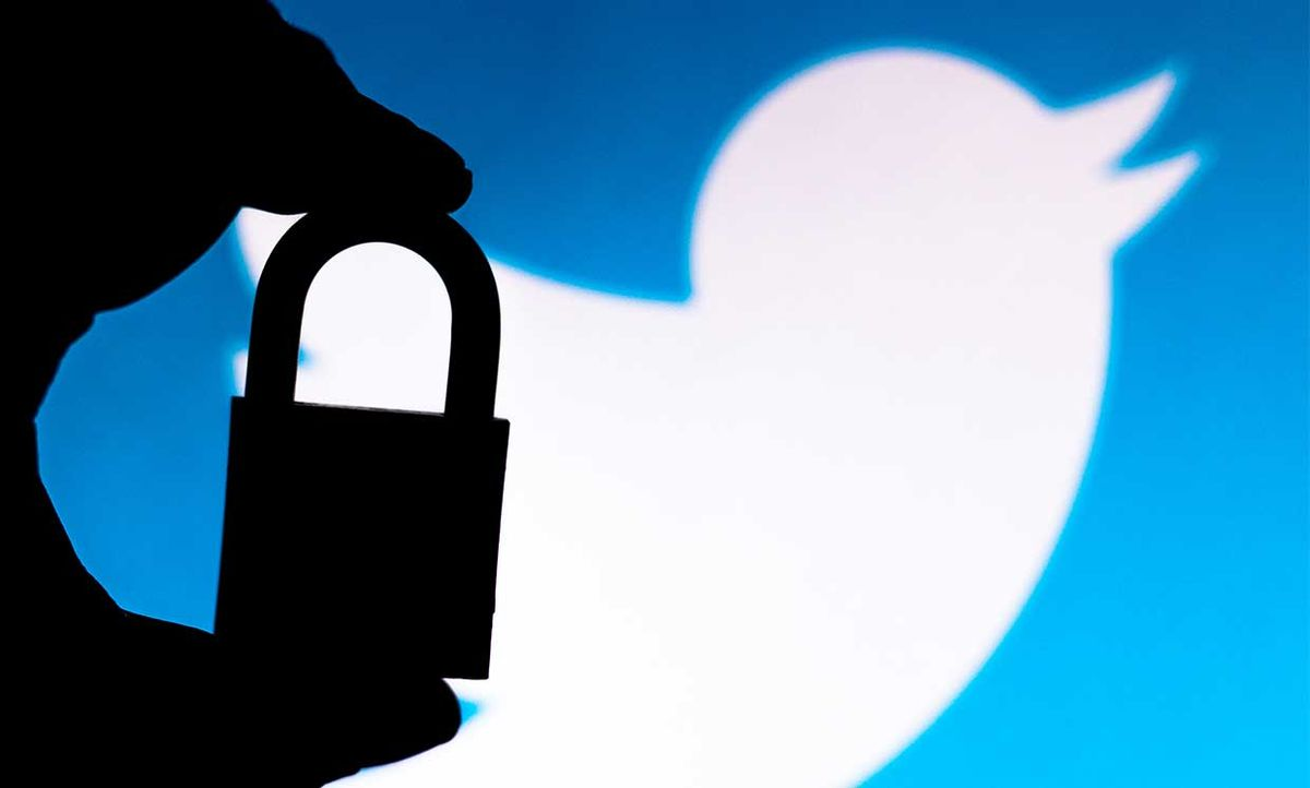 Conceptual photo of someone holding a lock in front of the Twitter logo