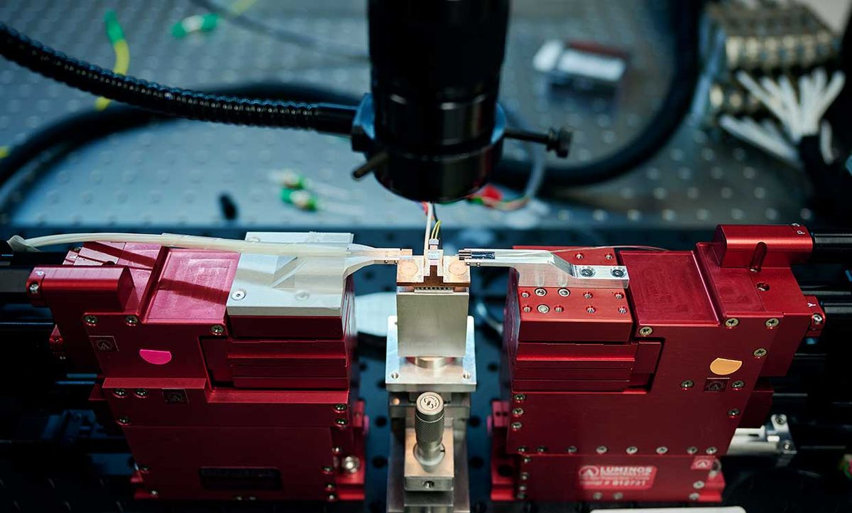A copper and silver colored sliver of metal sits on a stand between two vice-like red-colored supports that direct thin fibers towards the sliver
