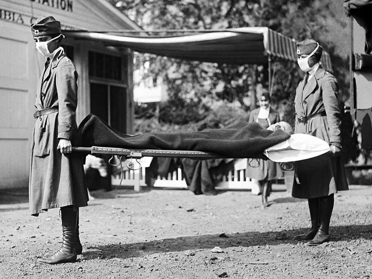 Two Red Cross nurses with a person on a stretcher during a demonstration at the Red Cross Emergency Ambulance Station during the influenza pandemic of 1918-1920, Washington DC, 1918.