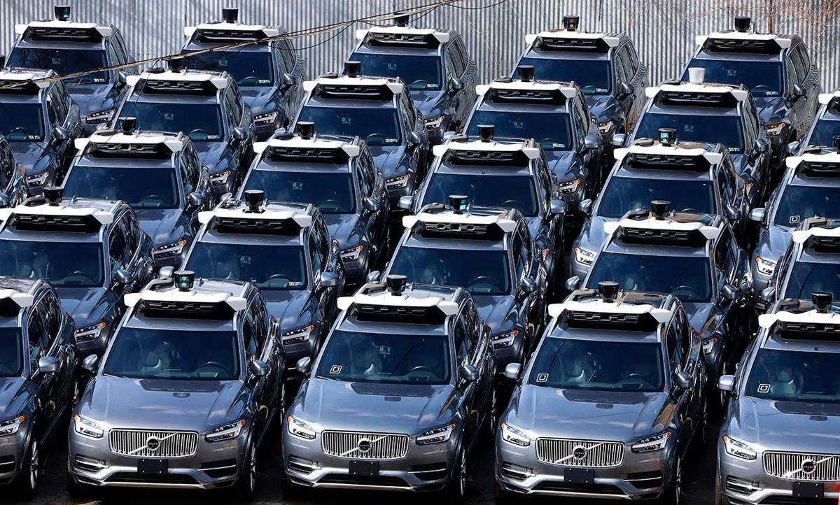 March 20, 2020 photograph shows a parking lot full of Uber self-driving Volvos in Pittsburgh.