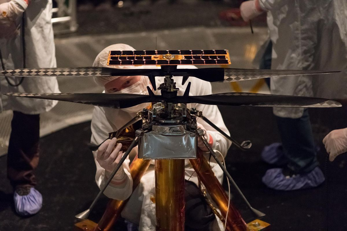 NASA engineers modifying the flight model of the Mars Helicopter inside the Space Simulator at NASA JPL.