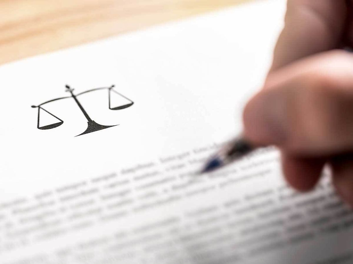 A hand holding a pen over a legal document.