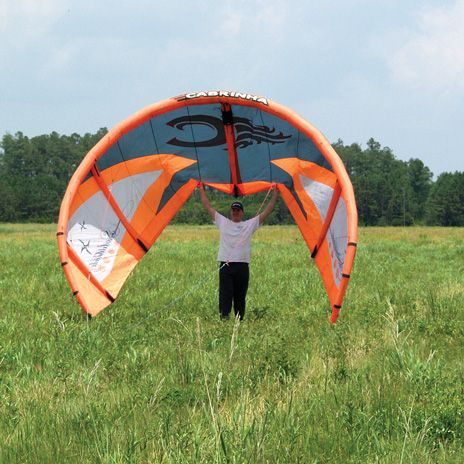 The author holds one of the off-the-shelf kiteboarding kites used to test the WindLift generator, waiting for the wind to pick up enough for a good launch.