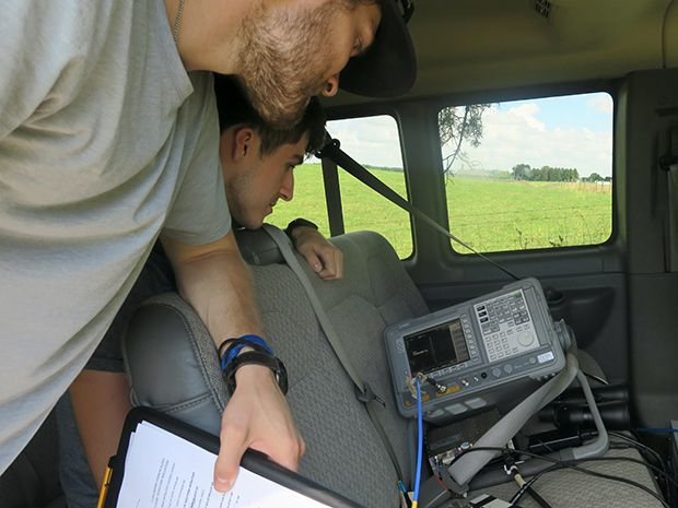 NYU students George MacCartney (left) and Jeton Koka (right) lean over the backseat of a van to observe the signal strength from their receiver on a Keysight E4407B spectrum analyzer, resting on a van seat, before ​recording a measurement.