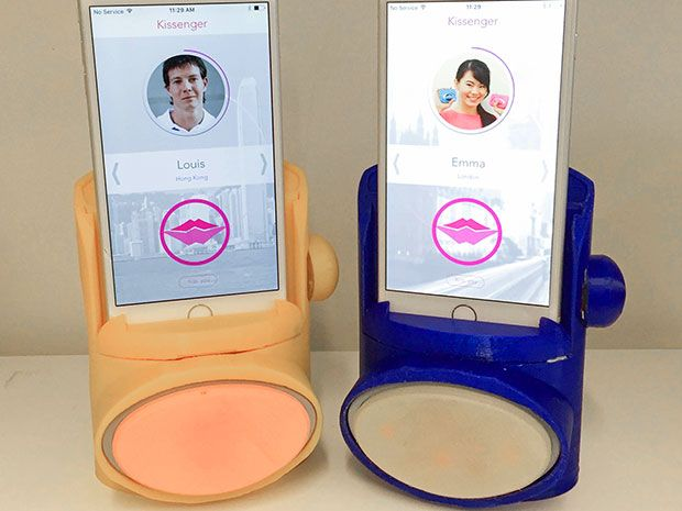 Two iPhones are connected to Kissenger devices. The phone screen shows the Kissenger app that enables kiss transmission during a video call.