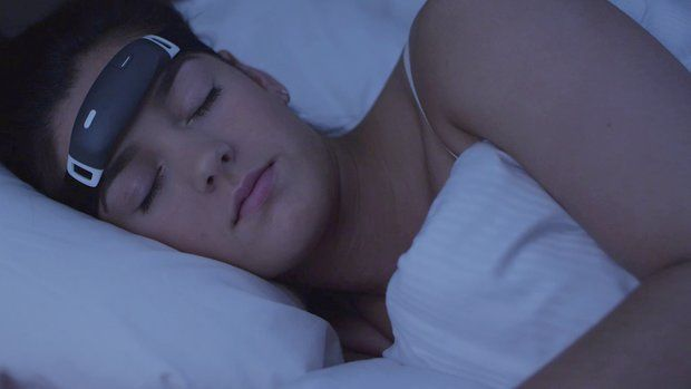 A woman sleeps in bed wearing a headband around her forehead.