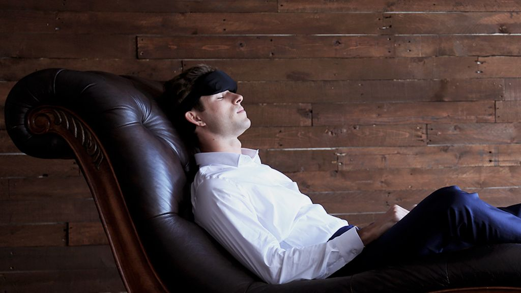A man sleeps on a couch wearing a black headband around his forehead.