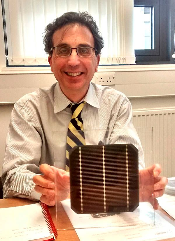 Photo of Oxford PV chief technology officer Chris Case holding a tandem silicon solar cell wafer featuring a perovskite coating.