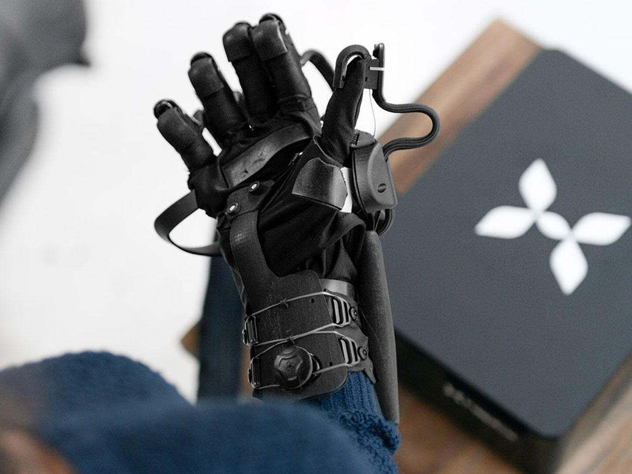 A photo shows a woman wearing the HaptX glove, holding it palm up over a table with the HaptX system below it.
