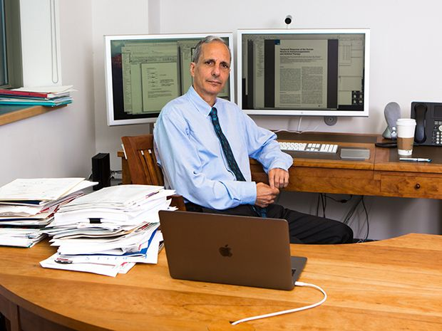 Doctor Robert Darnell sits behind his desk at the New York Genome Center