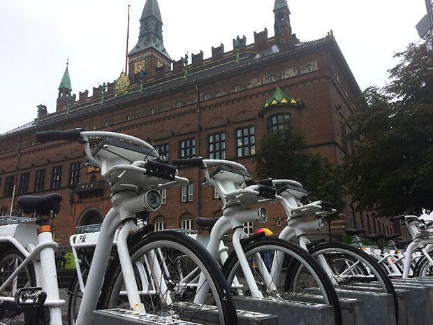 A row of white electric bicycles in front of a stately brick building in Copenhagen.