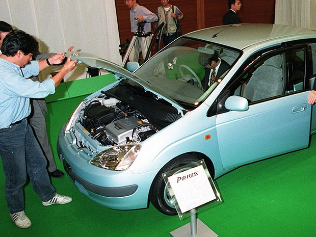 man inspects engine of 1997 Toyota Prius car