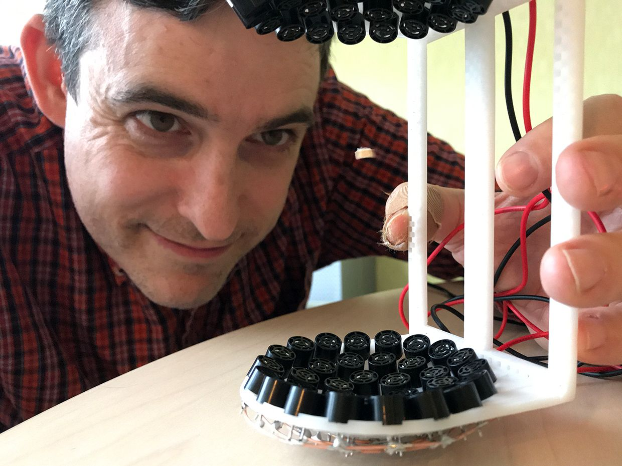 Photo of Stephen Cass holding the mounted 72 ultrasonic transducers in a 3D-printed frame.