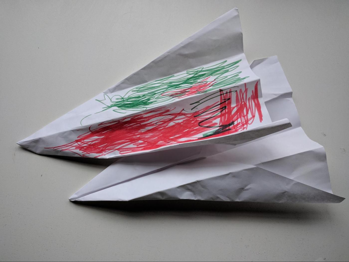 Two paper airplanes that a child gave to DragonBot.