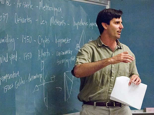 A man (Mark Jacobson) gesticulates in front of a blackboard.