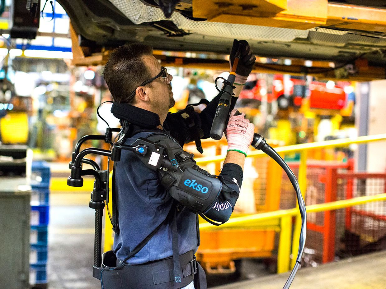 A worker on a car assembly line is wearing an upper-body exoskeleton as he lifts a tool overhead to work on a suspended chassis.