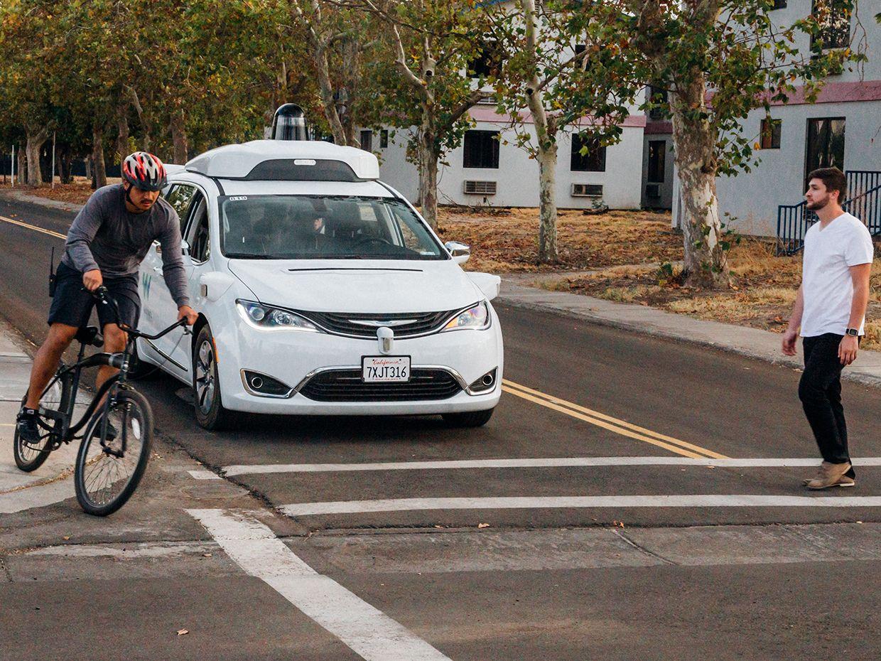 A cyclist crossses in front of a self-driving car at Waymo's test facility.