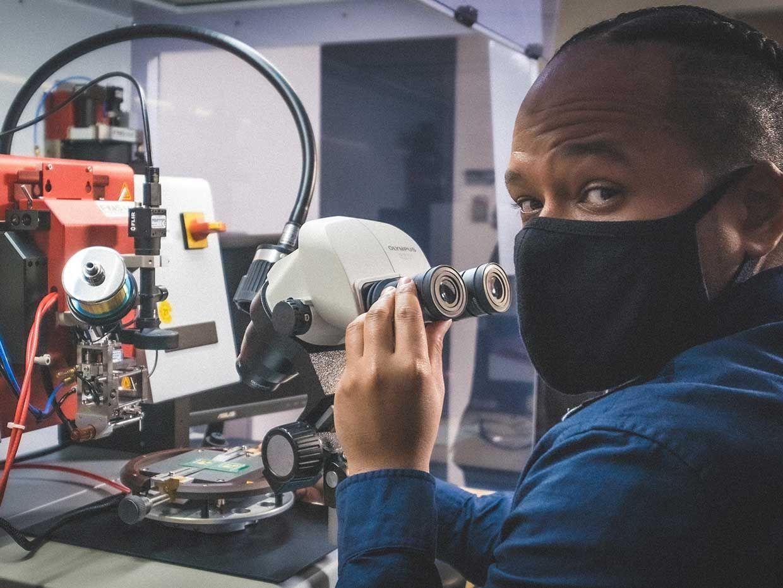 Image of Kenny Cardoso looking through photonics machinery.