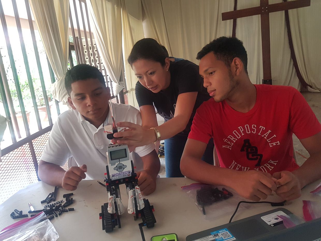 Placing a head (IR sensor) on the Lego Robot. Photo by Angelica  Calderon. In this photo, Rafael Moreno (left), Hassel Quiel (right) and Victoria Serrano (center)