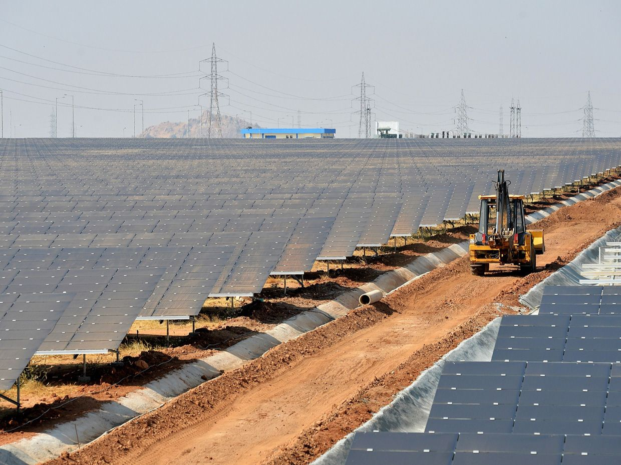 Photo of a construction vehicle driving in a solar panel farm.