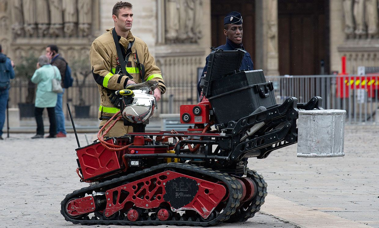 Firefighters are seen with a robot firefighter called Colossus, made by French robotics company Shark Robotics, outside Notre-Dame Cathedral on April 16, 2019 in Paris, France.