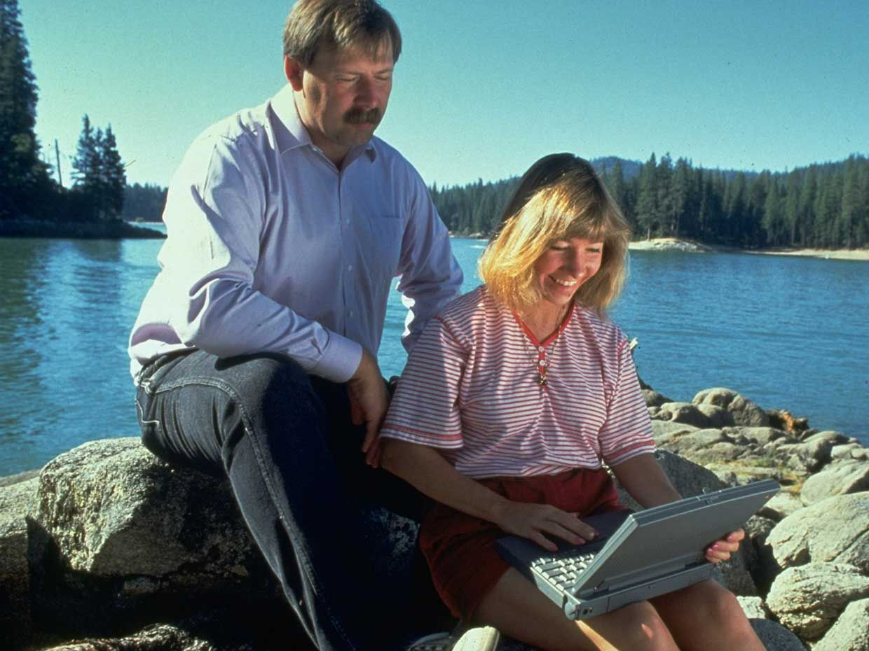 1993 photo of Sierra Systems founders Ken & Roberta Williams sitting on rocks on lakeshore using laptop computer.