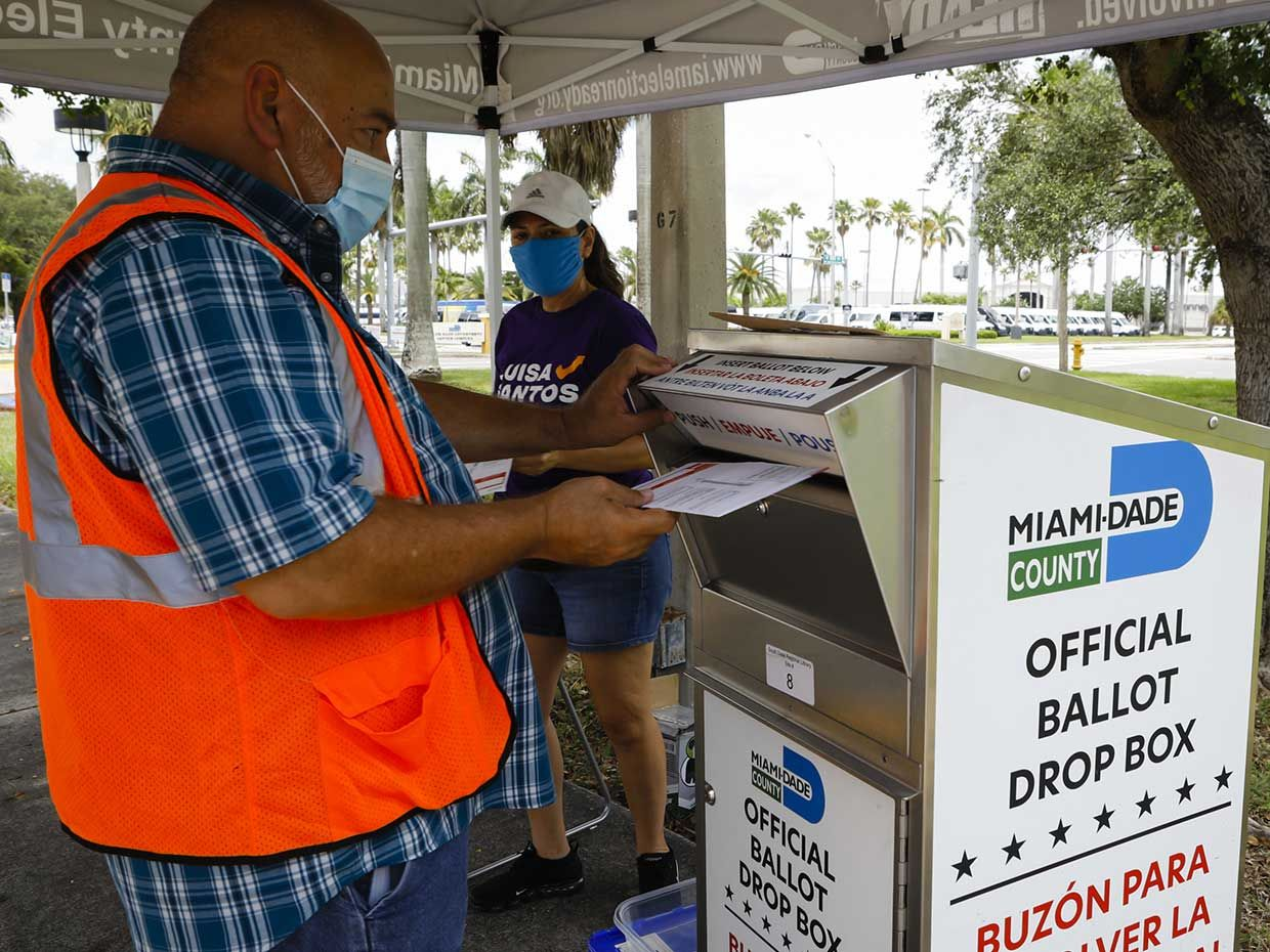 An election official wearing a protective mask drops off a mail-in ballot in a drop box at a polling location in Miami, Florida, U.S., on Tuesday, Aug. 18, 2020.