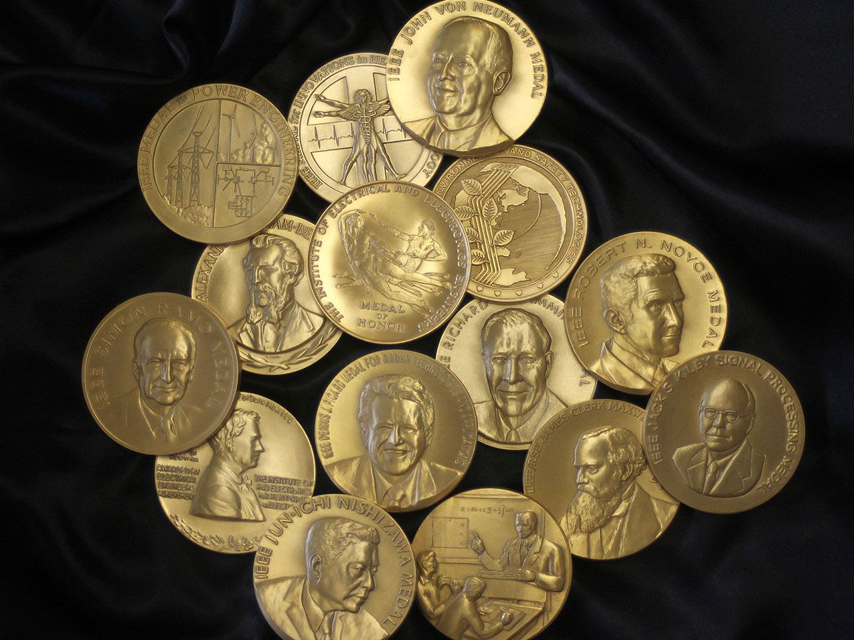 A group of gold IEEE Medals on black background.