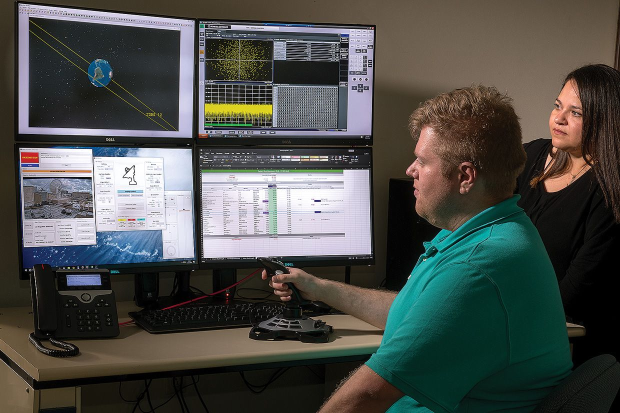 NASA engineers Cameron Seidl and Janette Briones run tests over TDRSS from this ground-station control room.