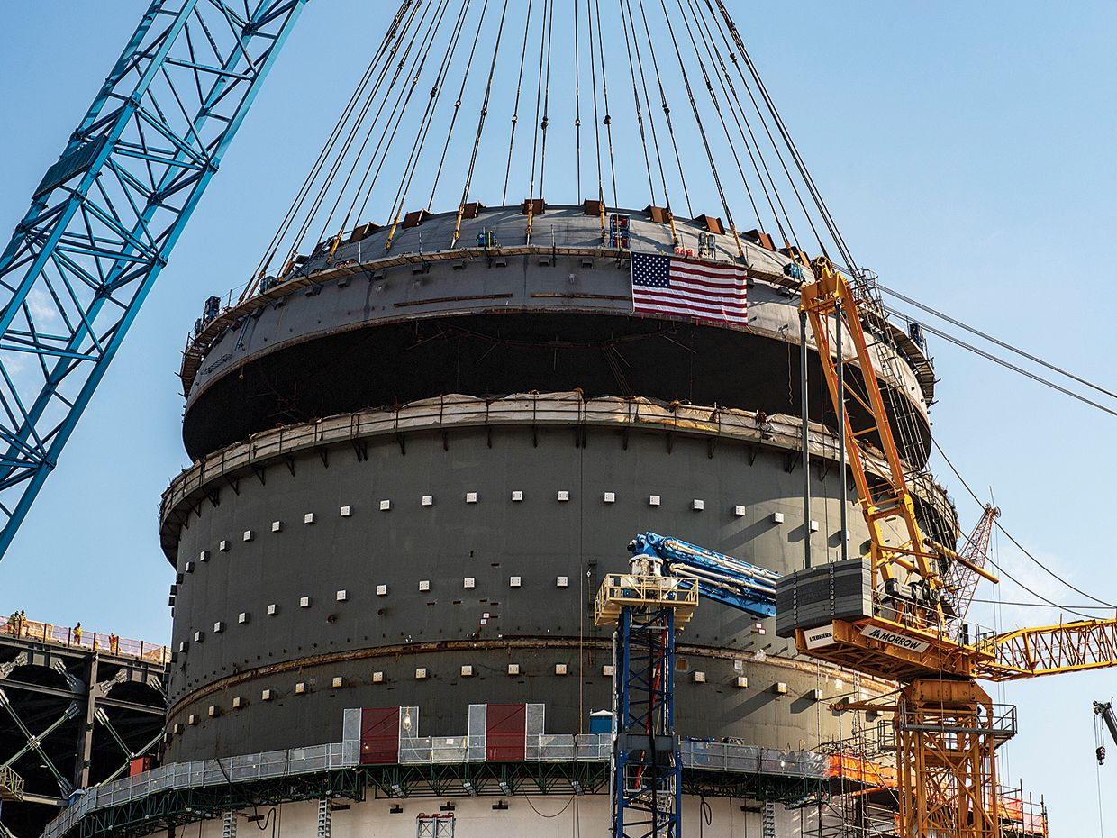 A crane lowers a heavy structure called a top head onto the Vogtle Unit 4 containment vessel in Georgia.