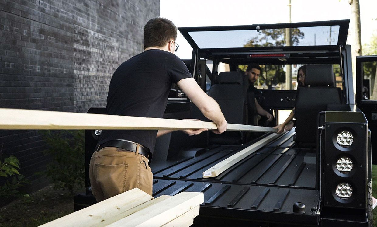 People load long pieces of lumber into the Bollinger Motors' B2 truck.