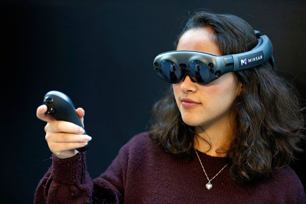 Photo of a woman wearing goggles and holding a controller.