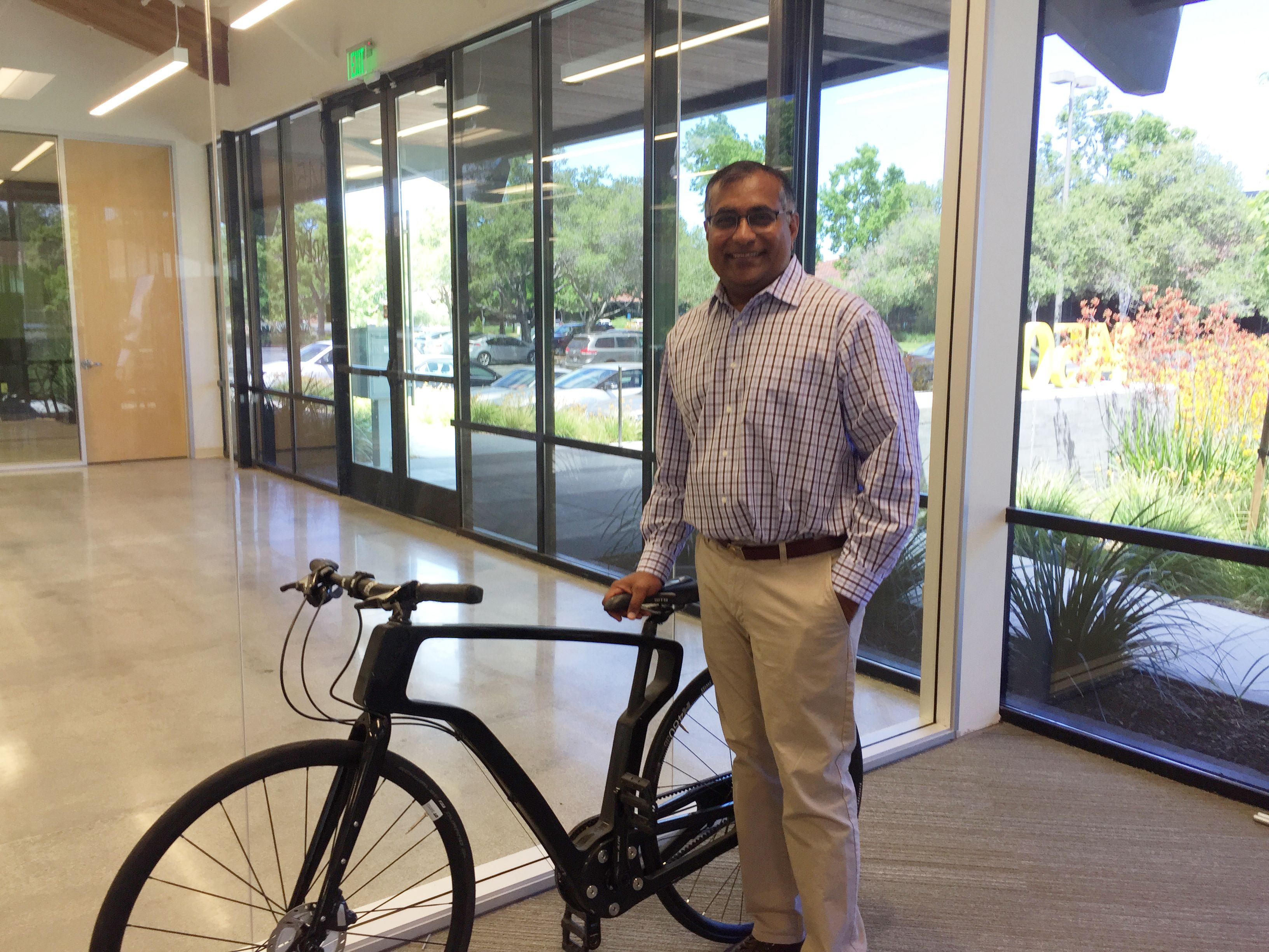 Image of Bheda in front of the bike with a 3D-printed carbon fiber composite frame.