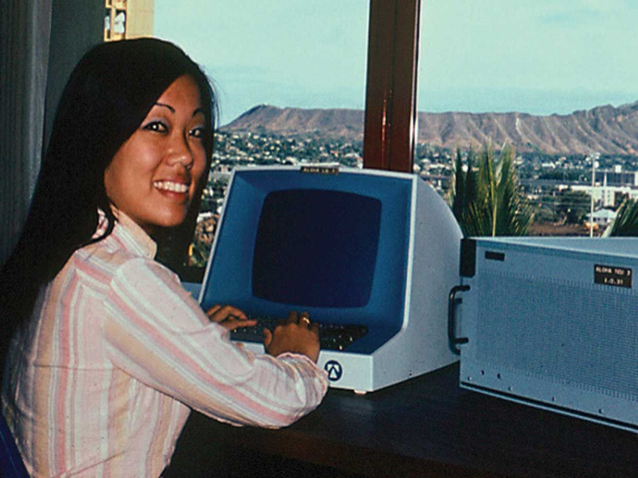 A woman sits in front of an AlohaNET computer in 1971.