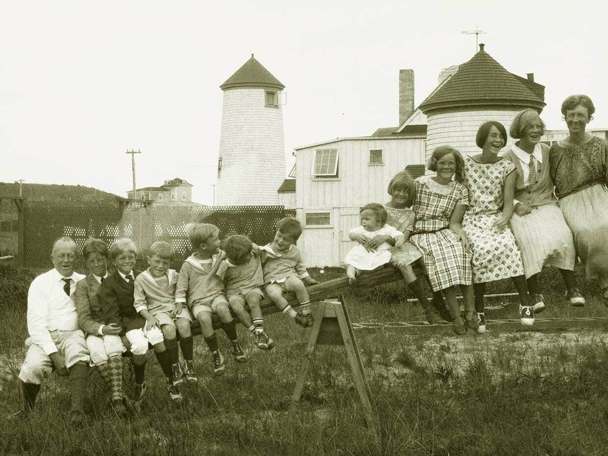 The Gilbreth family sits atop a see-saw while they spend their 1923 summer in an old lighthouse on Nantucket Island.