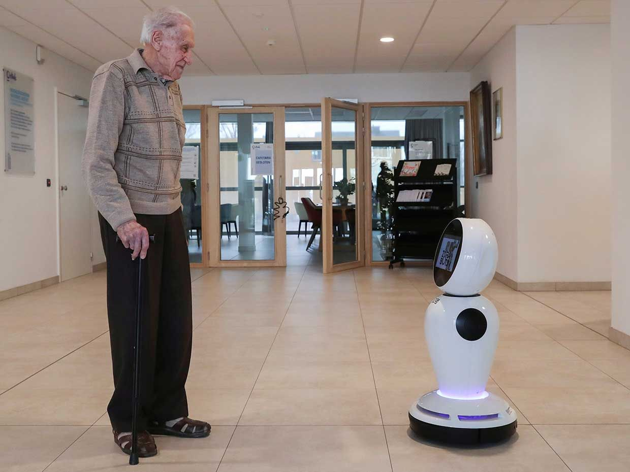 In Ostend, Belgium, ZoraBots brought one of its waist-high robots, equipped with cameras, microphones, and a screen, to a nursing home, allowing residents like Jozef Gouwy to virtually communicate with loved ones despite a ban on in-person visits