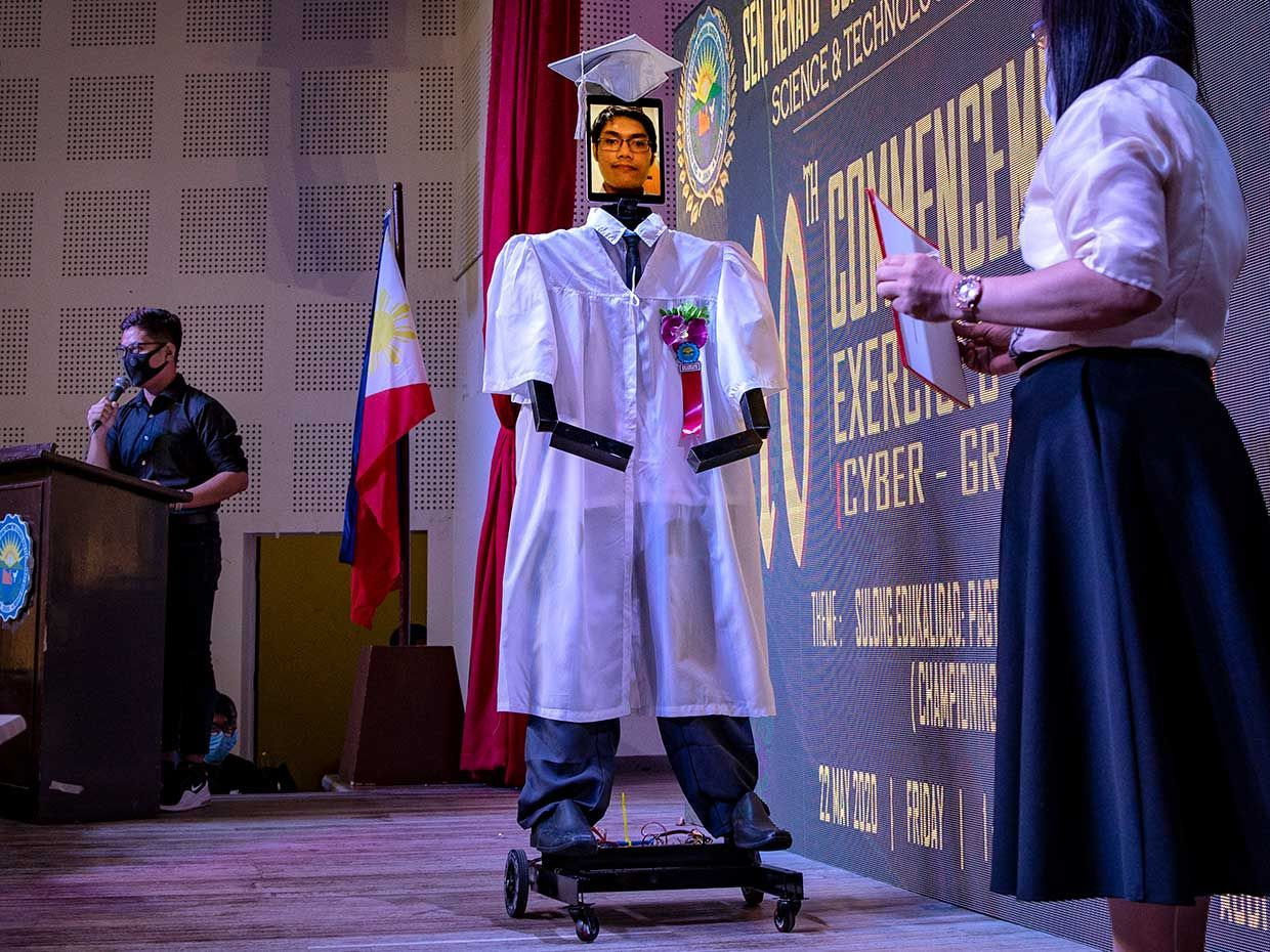 """In Manila, nearly 200 high school students took turns """"teleporting"""" into a tall wheeled robot, developed by the school's robotics club, to walk on stage during their graduation ceremony"""