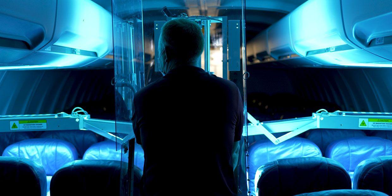 Man shining UV lights on airplane seats.