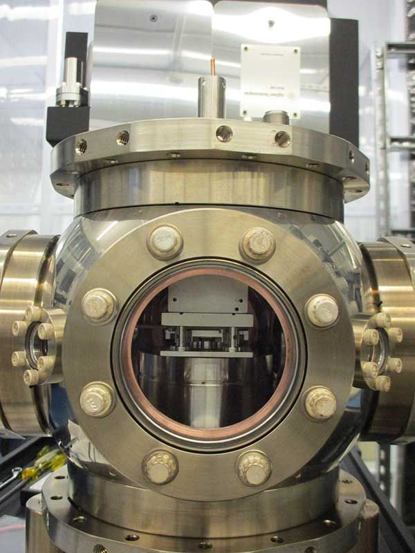 A vacuum chamber encloses the ion trap to protect the ultrasensitive ions from interactions with gas particles and from thermal and electromagnetic noise that might change their states, effectively crashing the quantum processor.