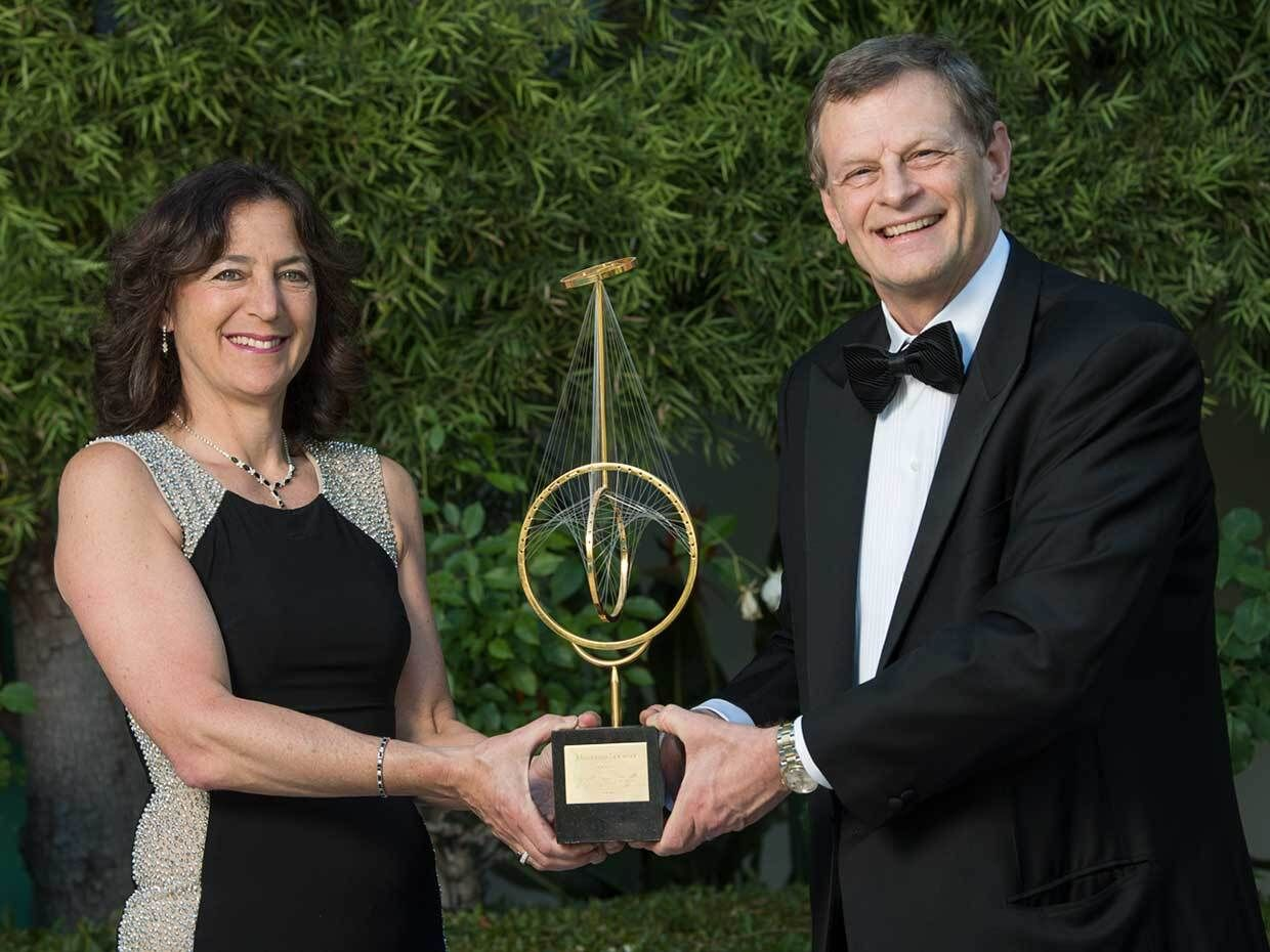Photo of two people holding an award.