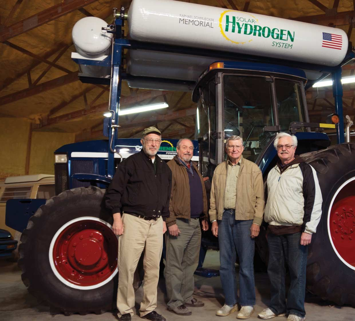 Four men standing in front of a tractor.