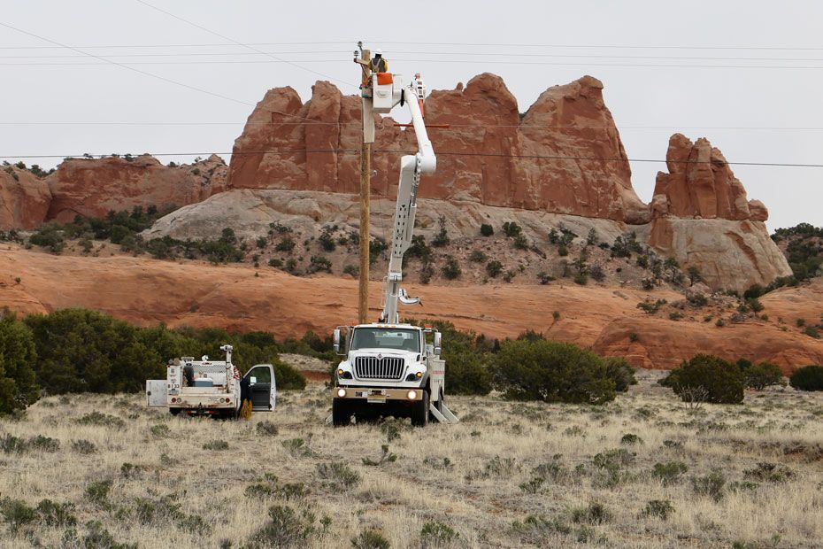 Workers from Massachusetts connect a distribution line in the Shiprock region.