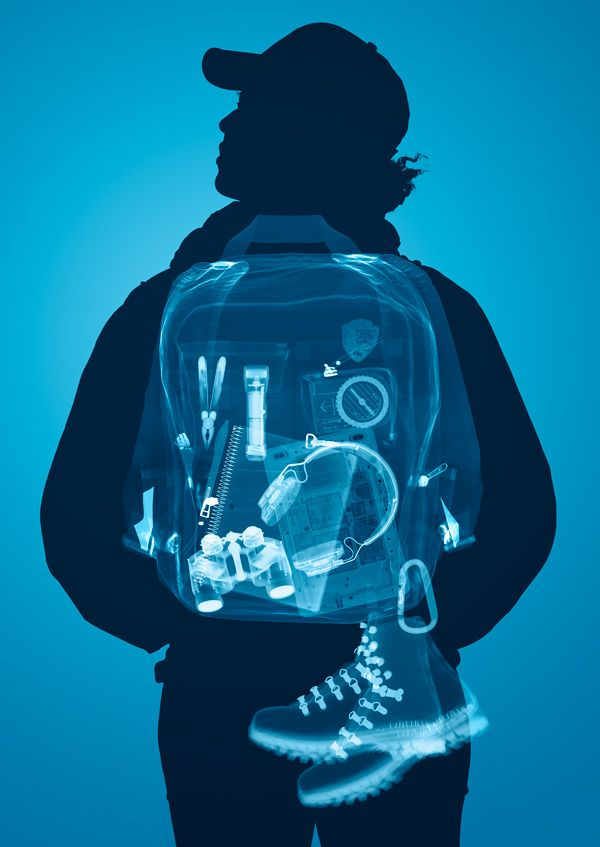 Young man's backpack is scanned, showing inside contents of electronics and tools.