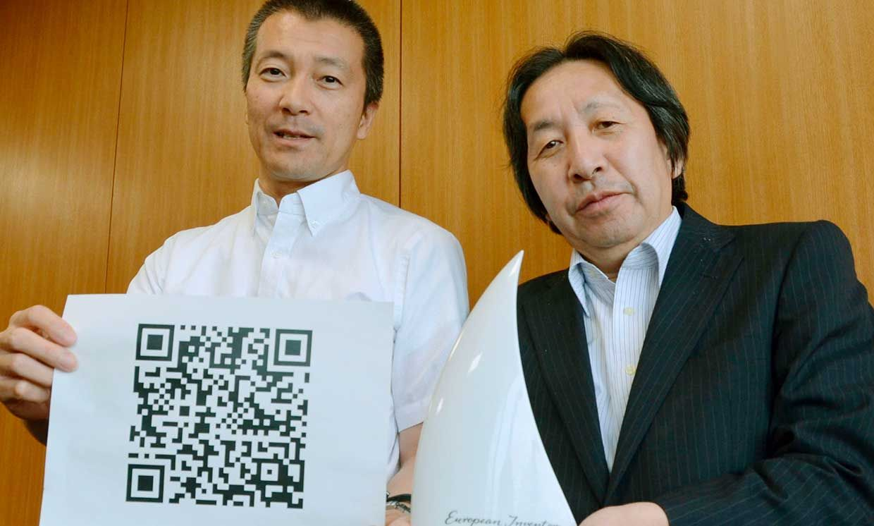 """Masahiro Hara (R) of Denso Wave Inc. and Takayuki Nagaya of Toyota Central R&D Labs. Inc. show their Popular Prize awarded by the European Patent Office for their invention of the square """"Quick Response Code,"""" or QR code."""