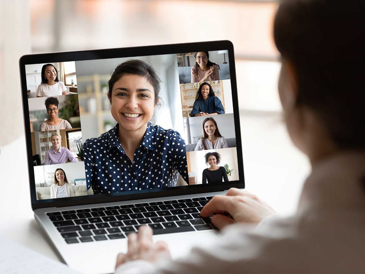 A woman who is talking on a group video call with a laptop.