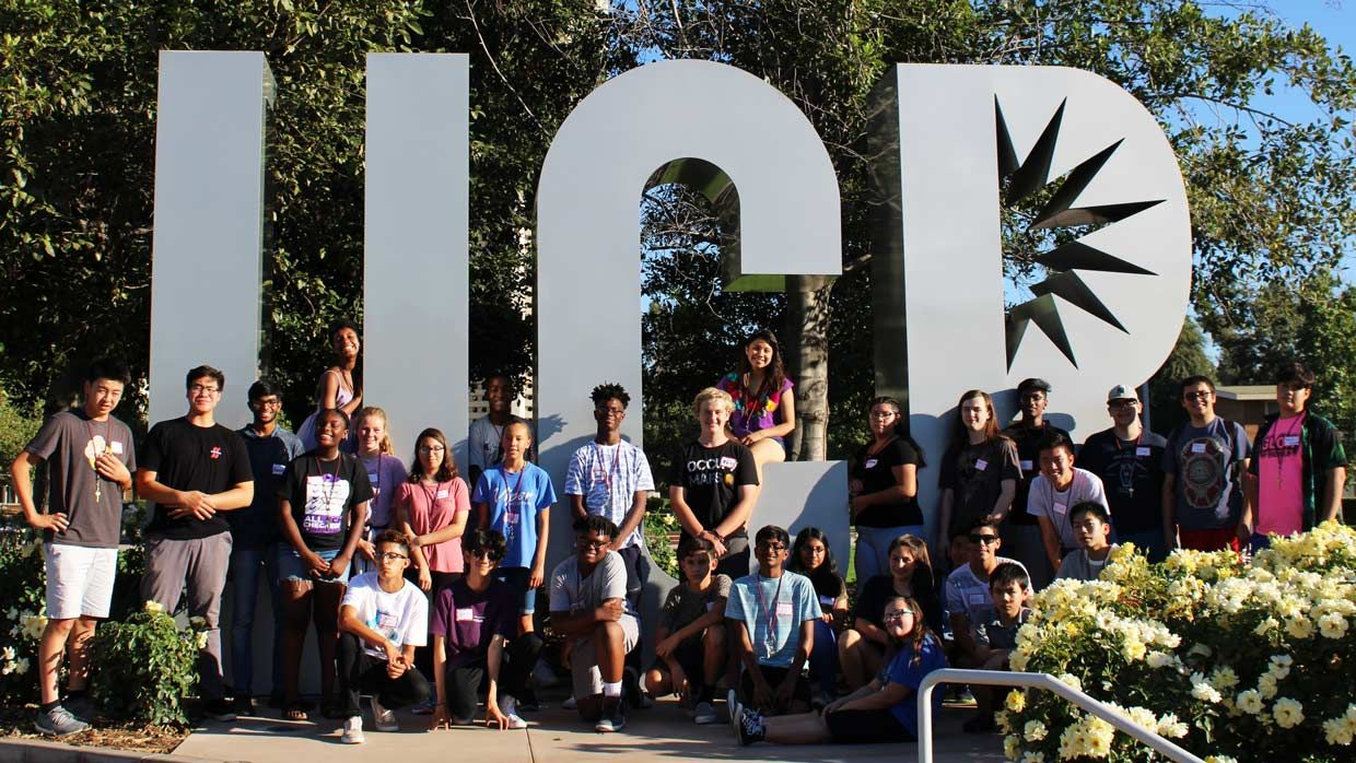 Photo of kids standing in front of a UCR sign