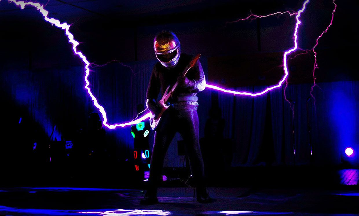Photograph from an ArcAttack show. A performer is in a wearable Faraday cage and Tesla coils produce giant sparks that look like they are coming out of the guitar.