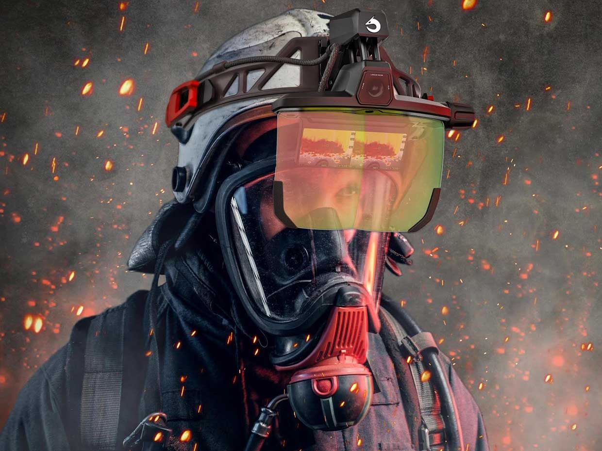 Photograph of a firefighter with the Longan Vision FVS augmented-reality visor showing thermal imaging